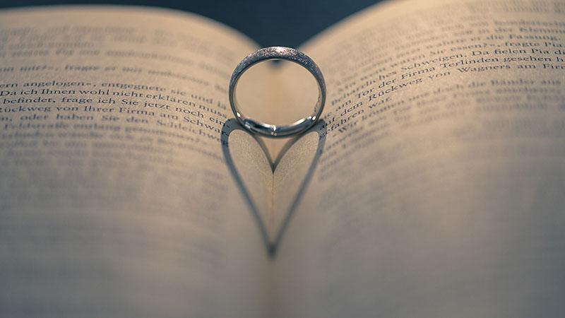 Der Schatten eines Rings formt ein Herz auf einem aufgeschlagenen Buch.