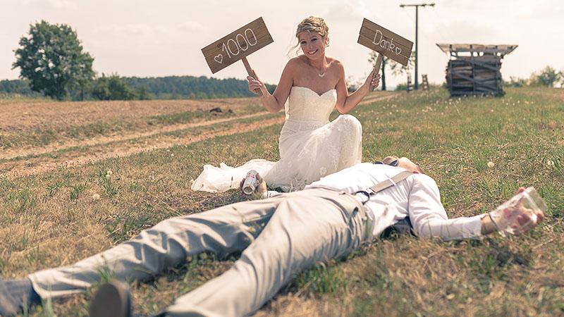 Braut hält Schilder 1000 Dank und Bräutigam liegt betrunken auf dem Boden.