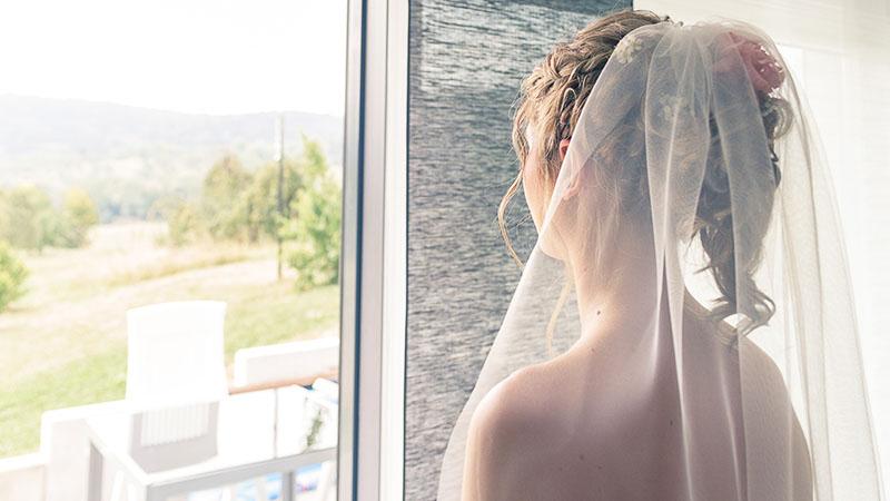 Braut mit Schleier schaut aus dem Fenster