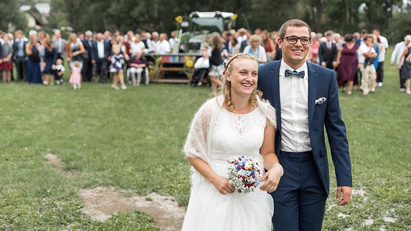 Brautpaar mit Hochzeitsgesellschaft im Hintergrund