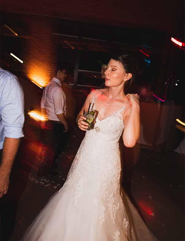 Eine Braut trinkt auf ihrer Hochzeitsfeier einen Cocktail