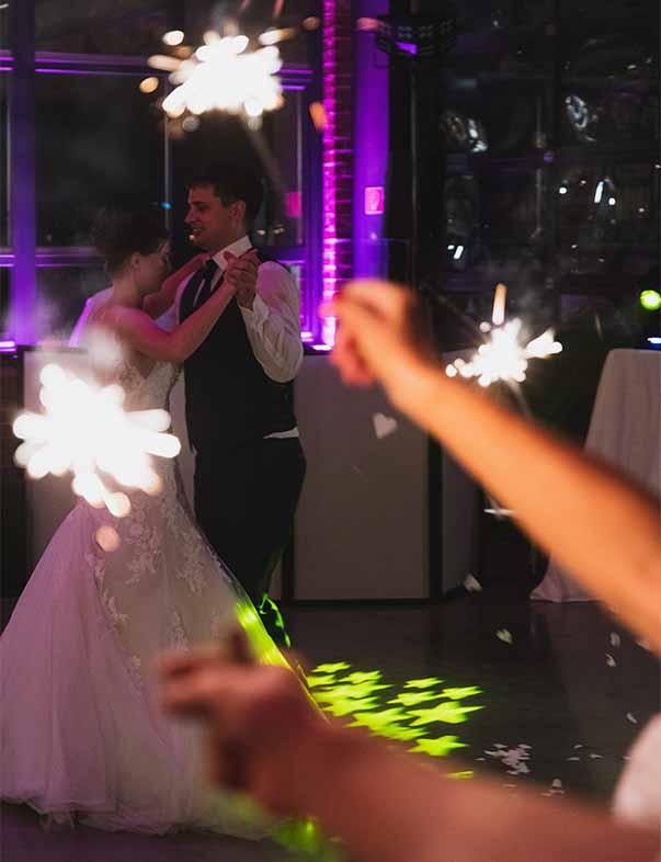 Brautpaar tanzt einen Hochzeitstanz, im Vordergrund sind zwei Hände mit Wunderkerzen